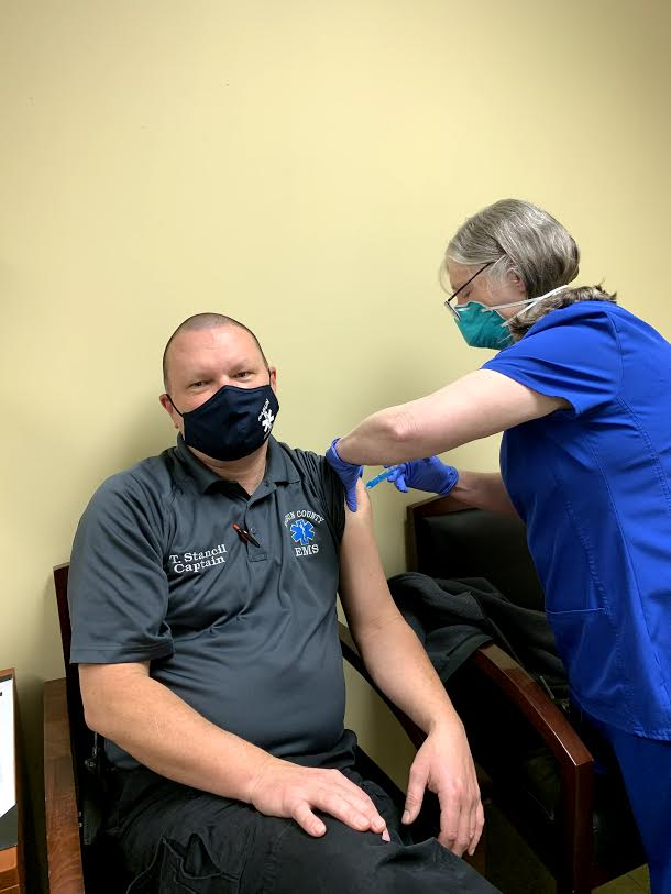 Photo courtesy Rabun County EMS. Captain Trampes Stancil, left, receives a COVID-19 vaccine administered by Josie Mosley at the Rabun County Health Department. EMS personnel are among the first to receive this vaccine.