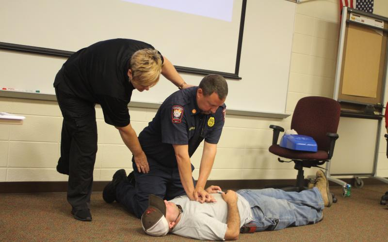 Megan Broome/The Clayton Tribune. Lt. Misty Houston, Rabun County Emergency Services, Justin Upchurch, assistant chief of Rabun County Fire Services and Hunter Hargrave, Rabun County Firefighter, give a lesson on how to administer chest compressions to students in emergency situations at Rabun County School's annual bus driver training on Thursday, July 25.