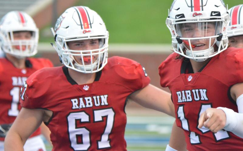 Rabun County offensive lineman Will Hightower (67) and quarterback Gunner Stockton (14) celebrate after a touchdown during the first half against Bremen in the Erk Russell Classic at Georgia Southern's Paulson Stadium in Statesboro last Saturday night. (Wayne Knuckles/The Clayton Tribune)