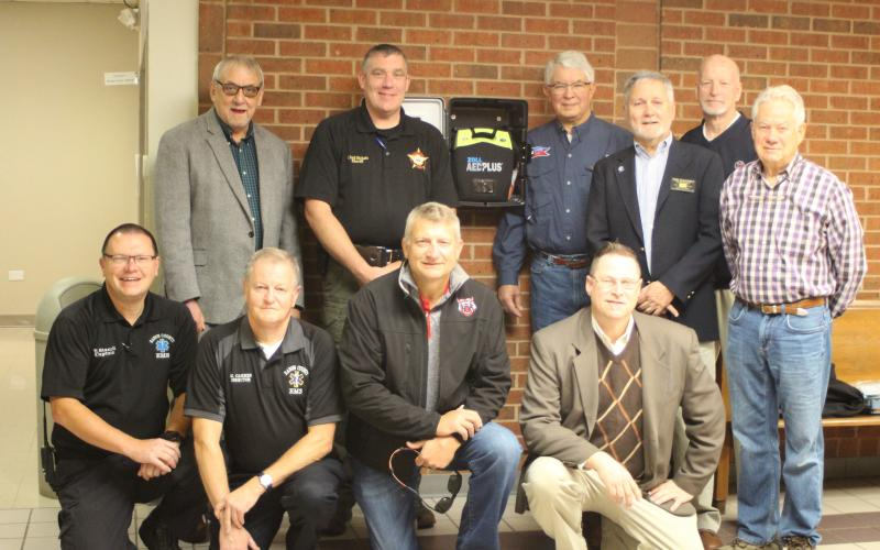 Megan Broome/The Clayton Tribune. The Rotary Club of Clayton has donated four Automated External Defibrillators to Rabun County EMS, two of which replaced old AED's at the courthouse. Front, from left, Trampes Stancil, EMS captain, Mike Carnes, EMS director, Darrin Giles, county administrator, Tony Penrose; Middle, from left, Tim Ranney, Rotary president, Ray Pagano; Back, from left, Wayne Knuckles, Sheriff Chad Nichols, David Tatum and Matt Mitcham.