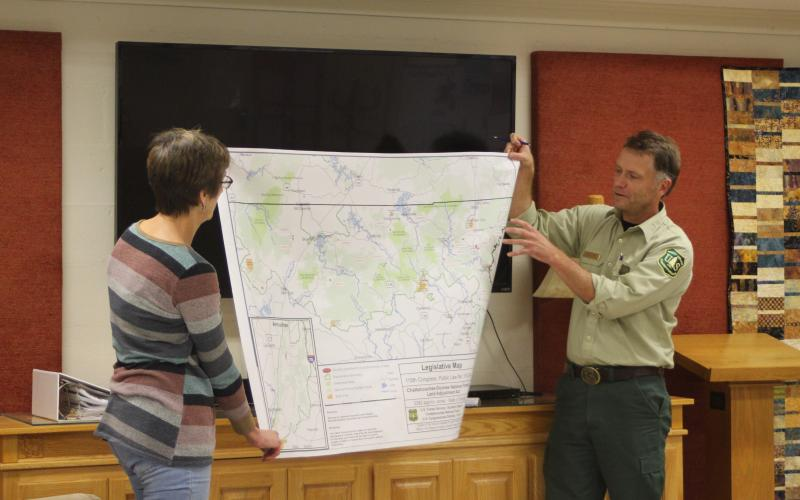 Megan Broome/The Clayton Tribune. Marie Dunkle, board president for Georgia ForestWatch, left, and Ryan Foote, district ranger for the Chattooga River Ranger District of the Chattahoochee-Oconee National Forest in Lakemont, hold up a map of National Forest System Land in Georgia potentially for sale. Foote points to the location of Rabun County, where approximately 1,229 acres of the roughly 3,841 acres is located.