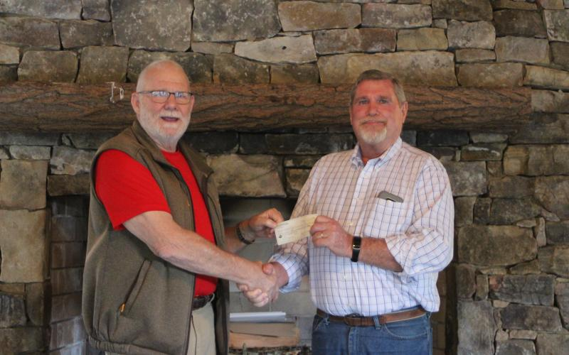 Megan Broome/The Clayton Tribune. Rocky Ford, left, President of Rhapsody in Rabun, presents a check to Dan McAfee, President of Habitat for Humanity of Rabun County, from the proceeds of the Rhapsody in Rabun Gala at an event held at the Lake Rabun Pavilion recently.