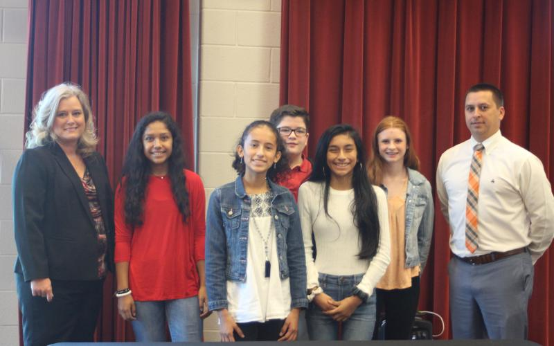 Megan Broome/The Clayton Tribune. Superintendent April Childers, left, Vanessa Balderas, Itzia Vasquez, Justin Cody, Melanie Mendoza, Roseanna Carver and assistant superintendent Jonathan Gibson attend the REACH signing ceremony in the Rabun County Band Room last Friday.