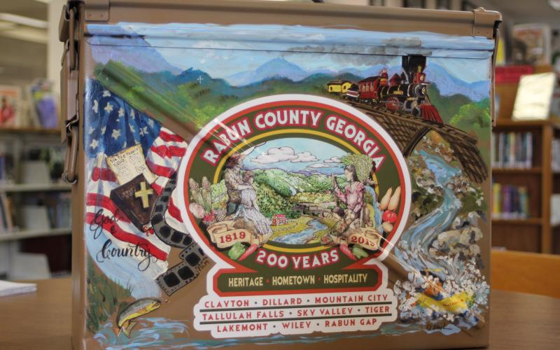 Megan Broome/The Clayton Tribune. The time capsule that will be buried for the Rabun County Bicentennial and opened in 100 years was painted by local artist Diane Rush. The time capsule is a military ammo box that was donated by Alan Price.