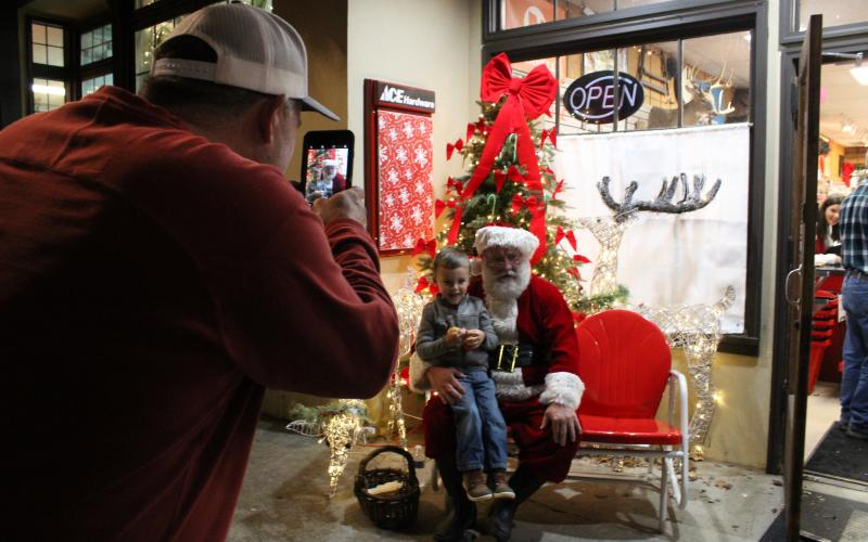 Rawlin Maxwell, 3, pays Santa Clause a visit while his grandfather Darren Dickerson snaps a picture during Christmas in Downtown Clayton