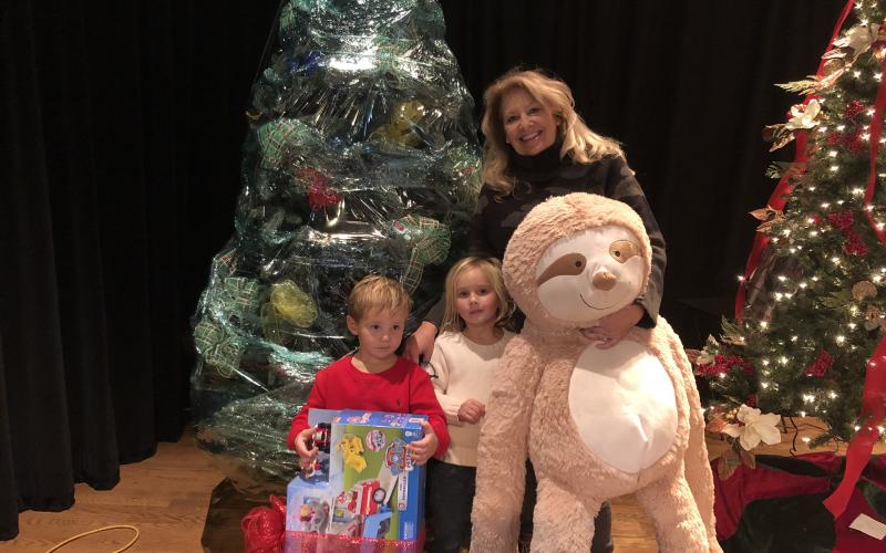 Shelly Lapp and her grand kids, Olivia and Riggs Bakes pack up their Christmas tree after winning the silent auction