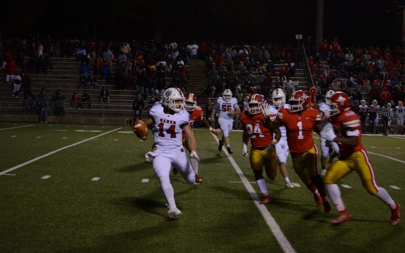 Rabun County quarterback Gunner Stockton (14) tries to avoid oncoming Thomasville defenders Friday night.