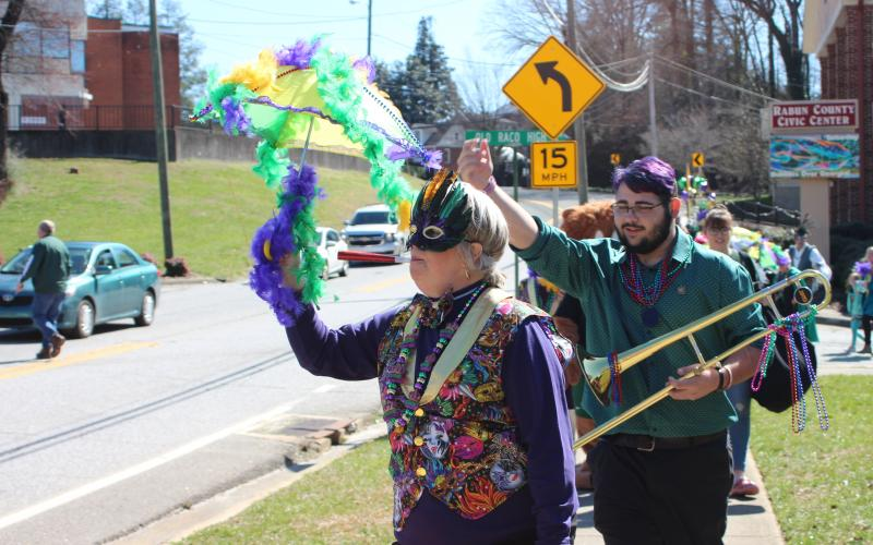Megan Broome/The Clayton Tribune. Teri Dobbs goes all-out and dances in the One Man Band parade for the second annual Mardi Gras sponsored by the Rabun County Chamber of Commerce on Saturday, Feb. 22. Kaleb Wilburn plays the trombone as the group travels through downtown Clayton.
