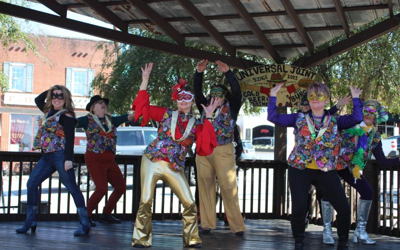 "Megan Broome/The Clayton Tribune. Nadine Bramlett, left, Cindy Chlupacek, Debbie Martin, Dina Vinson, Mary Baer and Sharon Purdy of the Rabun Entertainers group performs a flash mob to the tune of ""Footloose"" on the stage of Universal Joint for Mardi Gras."
