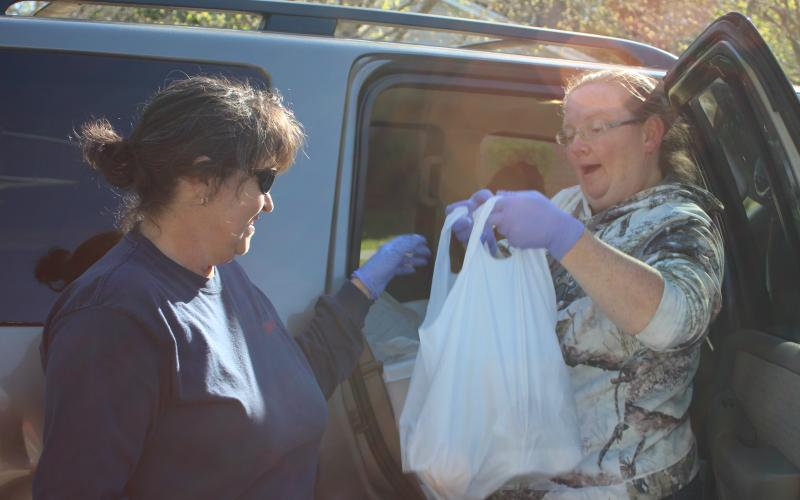 Megan Broome/The Clayton Tribune. Shannon Speed, left, and Melissa White distribute meals to elderly Rabun County residents on Monday as part of the Meals on Wheels program run by the Rabun County Senior Center. Enough meals for five days are being delivered by employees on Mondays in order to limit potential exposure of the COVD-19 virus to elderly residents.