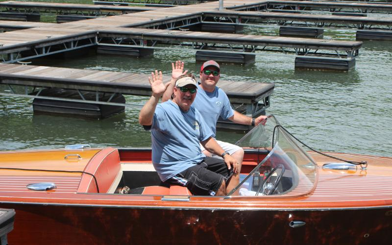 "Megan Broome/The Clayton Tribune.Fred Beck, left, and Hunter Hargrave showcase Beck's 1959 Chris Craft wooden boat named ""Tallulah"" at LaPrade's Marina following Lake Burton's first-ever Wooden Boat Parade. The whole boat is completely original and has been on Lake Burton its entire life."