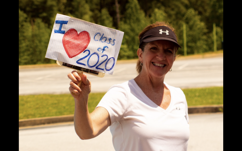 Photo courtesy Rabun County Schools. Jane Johnston, RCHS math teacher, shows her support for the Class of 2020. Rabun County High School seniors picked up their senior packets of their cap, gown, and care package last Friday. Family, friends, school officials and community members show their love to the Class of 2020 by decorating cars, holding up signs and waving and cheering as cars go by.