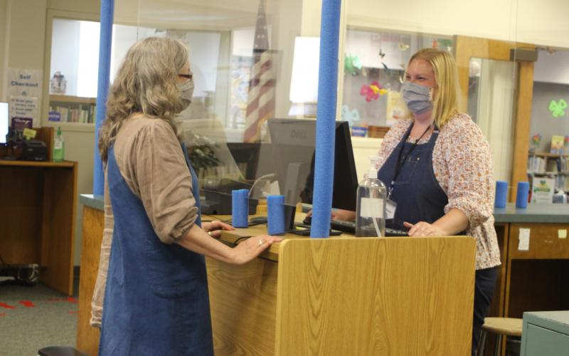 Megan Broome/The Clayton Tribune. Peggie Wilcox, circulation clerk, left, and Melissa Poslusny, senior clerk, demonstrate checkout procedures amidst the library's new contact precautions during the soft reopening of the Rabun County Library after being closed due to COVID-19.
