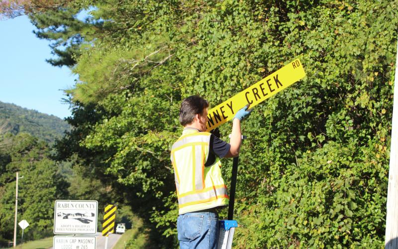 Megan Broome/The Clayton Tribune. Keith Yunger, sign technician for the Rabun County mapping department, replaces one of the road name signs located on Warwoman Rd. that was stolen on Labor Day weekend.