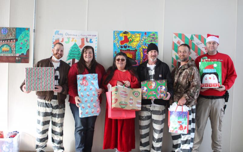 Megan Broome/The Clayton Tribune. Austin Groom, left, Captain Beth Darnell, Officer Patti Saunders, Joshua Arnold, Johnny Riddle and Officer Nathaniel Cross pass out Christmas gifts to the children of inmates on Saturday. They stand in front of the Christmas card made by inmates in C-Pod (center), who won the decorating contest.