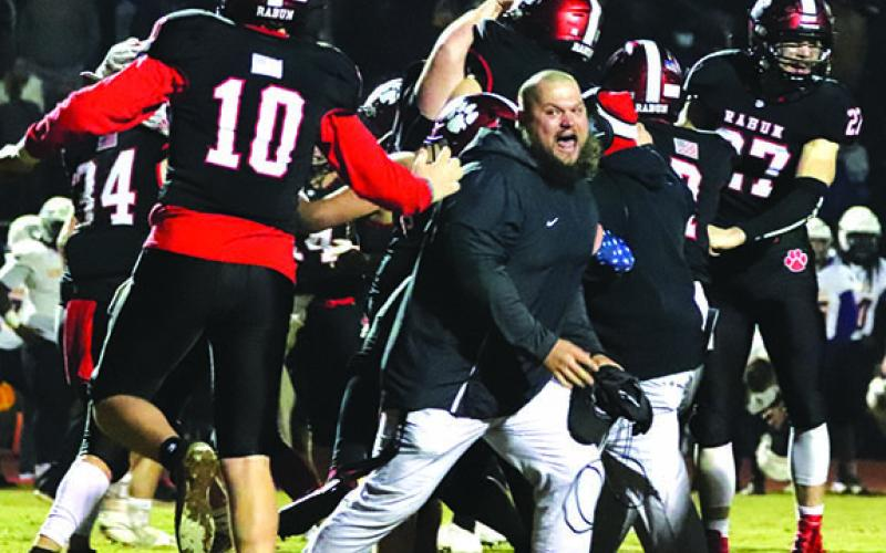 Rabun County Assistant Coach JayJay White joins the celebration after the Wildcats defeated Bleckley 27-24 in overtime last week. The Wildcats need to win one more game Friday night to earn the right to travel to Atlanta and play for a state championship.
