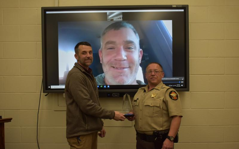 Photo courtesy Rabun County Sheriff's Office. Chief Deputy Scott Cheek, left, presents the Deputy of the Year award to Deputy Tony Parrish in December. Sheriff Chad Nichols participates via video call.