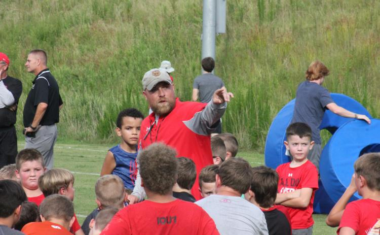 Rabun County running backs coach Andy Mahaffey directs players toward the next position station during the football team's Future Wildcats Camp at the team's practice field in Tiger on Monday night. (Glendon Poe/The Clayton Tribune)