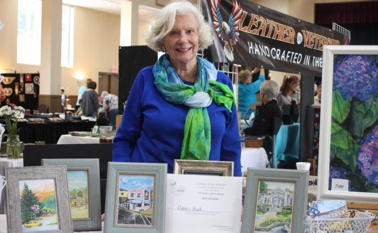 "Diane Rush displays her certificate for winning ""Peoples Choice Award"" for her paintings of historic buildings of Rabun County at the Painted Fern Festival of Art hosted by the North Georgia Arts Guild at the Rabun County Civic Center on July 13-14."