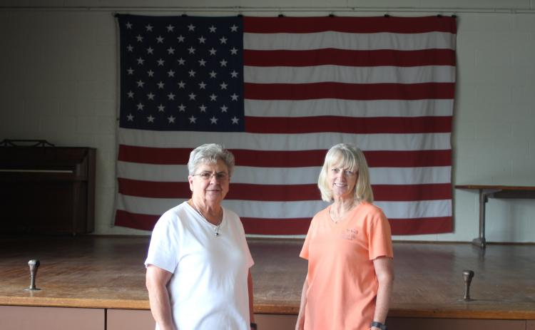 Grace Watts, mayor of Mountain City, left, and Brenda Cannon, city clerk, stand in front of the stage on new flooring at Mountain City's city hall where the Bicentennial square dance will take place on Saturday, July 20