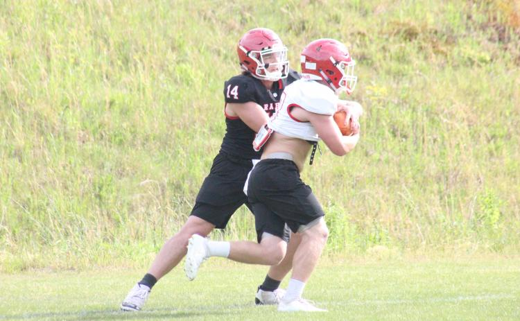 Rabun County quarterback Gunner Stockton, left, hands the ball off to running back Brody Jarrard during a practice in May. (Glendon Poe/The Clayton Tribune)
