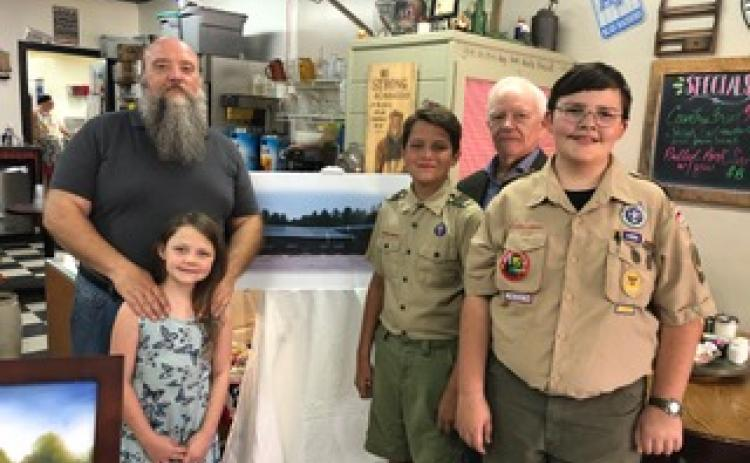 Wayne Knuckles/The Clayton Tribune. Ron Broz and Kaitlyn Craig, along with Tom Buckridge and local Scouts Alex Dizon and Liam Broz, show a rendering of a proposed new youth facility for Rabun County at a capital campaign kickoff last recently at Sunday Diner.