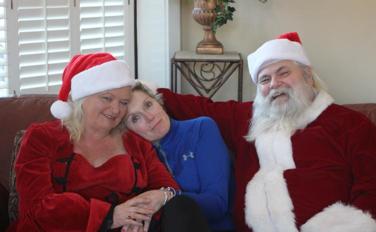 Megan Broome/The Clayton Tribune. Wanda Findley, middle, poses for a picture with her friends and neighbors MaryJane Phillips and Thomas Phillips, who travel around Georgia every year to portray Santa and Mrs. Claus. They give out presents to special needs and terminally ill children.