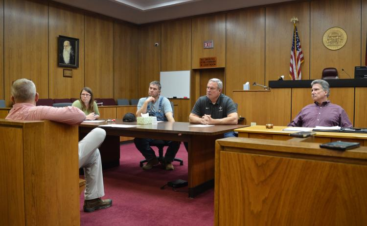 Wayne Knuckles/The Clayton Tribune. From left, County Clerk Linda Ramey and commissioners Will Nichols, Kent Woerner and Greg James at last Thursday's emergency meeting of the Rabun County commission.