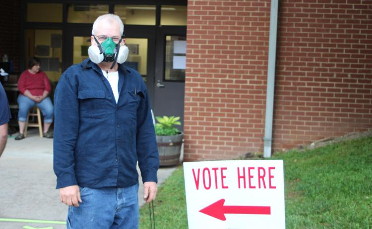 Megan Broome/The Clayton Tribune. Charles Wilkins wears a respirator mask as he participates in early voting at the Rabun County Board of Elections Office Monday. Voters are required to stand six feet apart as one person at a time goes into the building to cast their ballot. These areas are marked with tape along the sidewalk. This is part of COVID-19 precautions mandated by the state of Georgia.