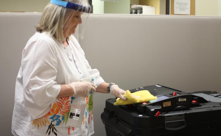 Megan Broome/The Clayton Tribune. Poll Worker Pat Hopper disinfects the entire voting area at the Board of Elections Office after each person finishes casting their ballot. Only one voter at a time is allowed inside the building for early voting as part of COVID-19 contact precautions.