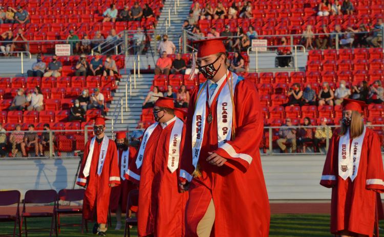 Wayne Knuckles/The Clayton Tribune. Under fair skies and a nearly-full moon, the Rabun County High School Class of 2020 received diplomas Saturday at Frank Snyder Memorial Stadium. Pictured: Andrew O'Brien, left, Cole Littrell and Will Hightower take their places.