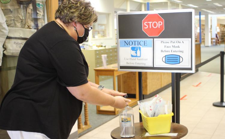 Megan Broome/The Clayton Tribune. The Rabun County Public Library reopened on Tuesday and patrons are required to wear masks while browsing and follow other health guidelines like sanitizing hands and following the direction arrows to maintain a six-foot distance.  Jennifer Buchanan, circulation supervisor, uses hand sanitizer to demonstrate measures patrons are asked to take upon entering the library.