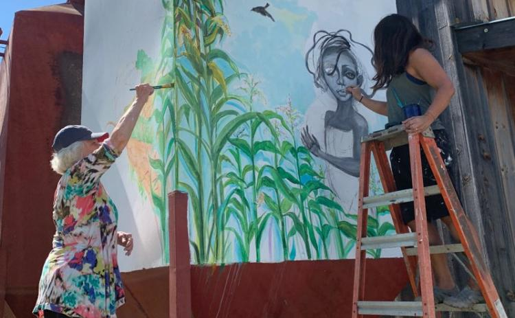 Daniela Cintron/The Clayton Tribune. Lizzy Falcón, right, paints with Diane Rush on one of the spaces outside the new The Lotus Gallery and Art Center, which plans to officially open its doors in 2021 to incite art with local and worldwide artists.