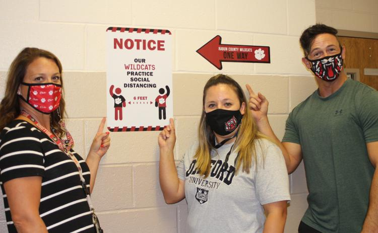 "Megan Broome/The Clayton Tribune. Lori Keller, left, Alicia Kilby and John Kilby produced a video parody of Aerosmith's ""Walk This Way"" as a fun way to show Rabun County Middle School students what to expect with COVID-19 precautions when school starts back. The video quickly went viral after being posted on social media."