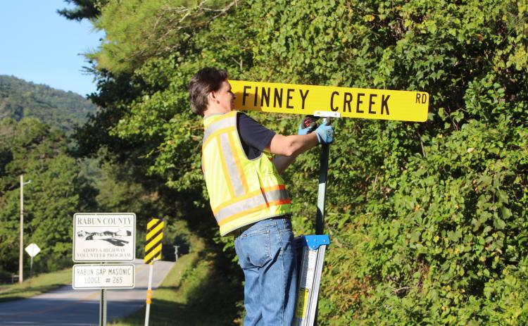 Megan Broome/The Clayton Tribune. Keith Yunger, sign technician for the Rabun County mapping department, replaces one of the road name signs located on Warwoman Rd. that was stolen on Labor Day weekend. A total of 80 signs were reported stolen, along with one stop sign and seven stop signs damaged. Yunger installs all of the road signs in the county.