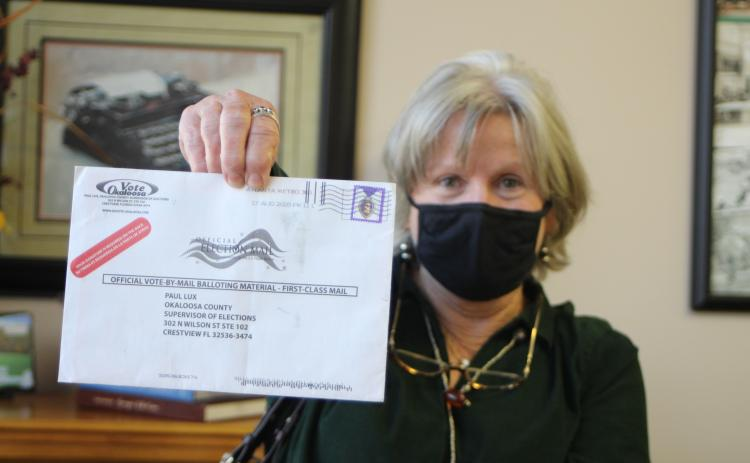 Megan Broome/The Clayton Tribune. Voter Pamela Wawrzyk holds up an absentee ballot that was returned by the post office for an unknown reason. She said that she and her husband Stephen found the ballot in their mailbox when they came back from Florida and it had no indication of the reason it was returned. She cautioned voters to be sure and check their ballot status to make sure their ballot is received by the elections office for their vote to be counted.